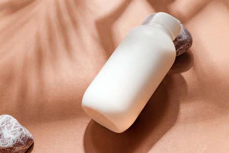 Close-up mockup bottle on papaya background.