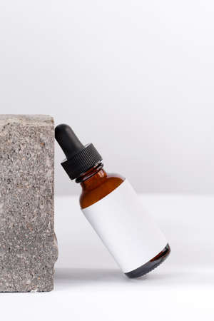 Close-up serum essence in glass bottle on stone background. Isolated skincare oil