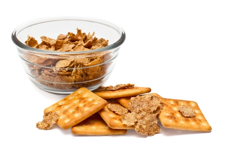 Corn flakes in a glass bowl and cookies on a white background photo