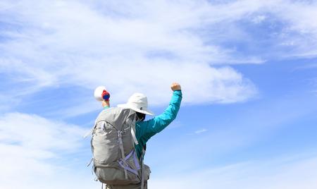 aerophone: backpacker shouting with loudspeaker on beautiful mountain peak