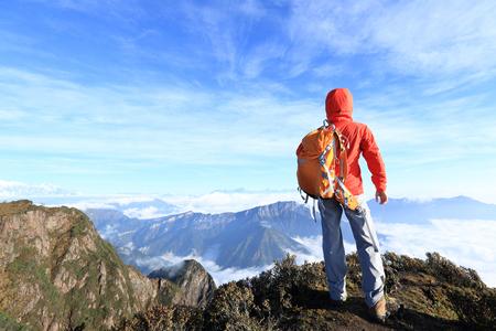 jokul: young determined woman backpacker hiking on mountain peak