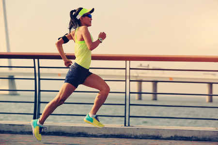 active listening: young fitness woman runner running at seaside