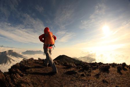 jokul: young woman backpacker hiking to beautiful mountain peak