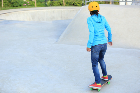 skateboard shoes: skateboarder woman skateboarding at skatepark Stock Photo