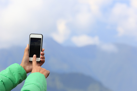 taking photo: woman hands taking photo with smart phone on mountain peak Stock Photo