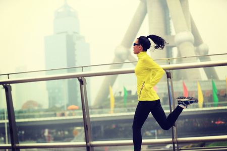 shanghai: young fitness woman runner running at shanghai city