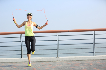 rope bridge: young fitness woman jumping rope at  seaside