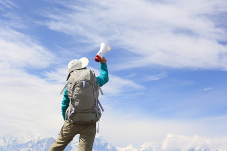 annoucement: young woman backpacker shouting with loudspeaker on beautiful mountain peak