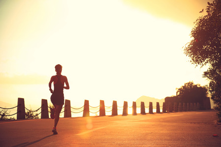 sunrise: young fitness woman running on sunrise seaside trail