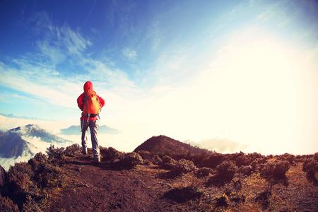 jokul: young woman backpacker hiking on mountain peak