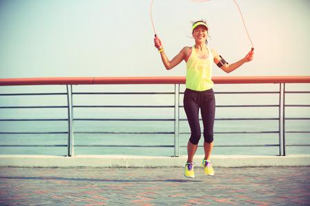 gente saltando: aptitud de la mujer joven saltando la cuerda en la playa
