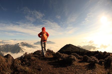estiramientos: excursiones mujer joven excursionista en pico de montaña
