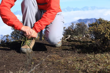 hiking boots: young woman hiker tying shoelace of hiking boots on mountain peak