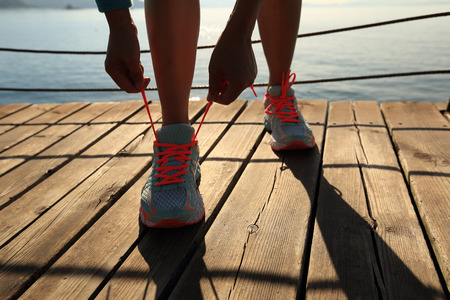 shoelace: young fitness woman runner tying shoelace at seaside boardwalk