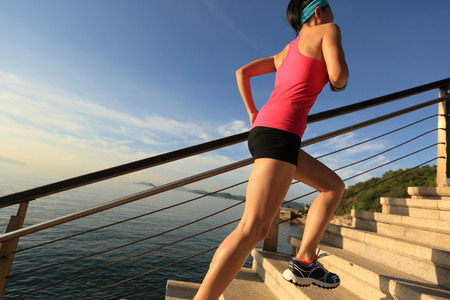 healthy: healthy lifestyle sports woman running up on stone stairs seaside