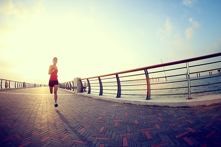 outdoor exercise: young fitness woman runner running at seaside