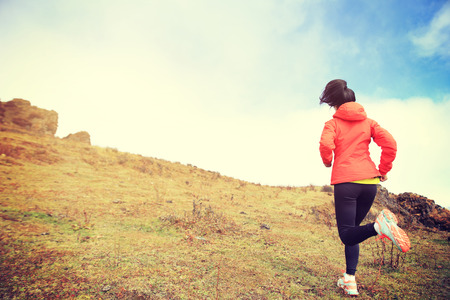 outdoor exercise: young woman trail runner running on mountain peak