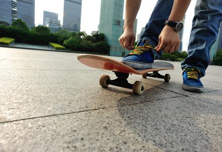 shoelace: skateboarder tying shoelace at city