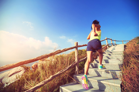 woman stairs: young fitness woman trail runner running up on mountain stairs