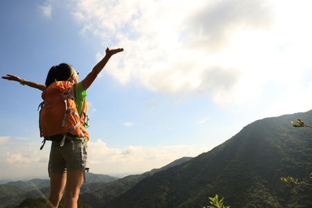 open arms: cheering young woman hiker open arms at mountain peak