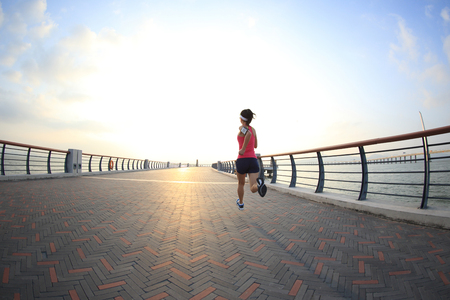 bewegung menschen: young fitness woman runner running at seaside