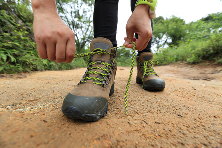 hiking boots: woman hiking tying shoelace on forest trail