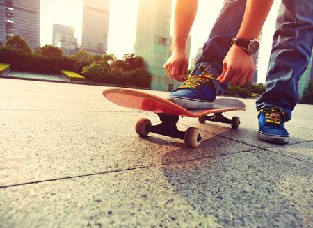 skateboard: skateboarder tying shoelace at city
