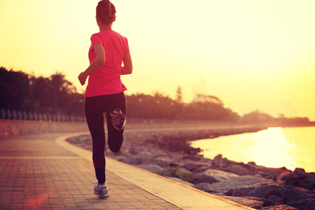 workout: young fitness woman running on sunrise seaside trail