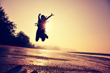 ?  ?   ?  jumping: animando excursionista de joven saltando en la playa de la salida del sol