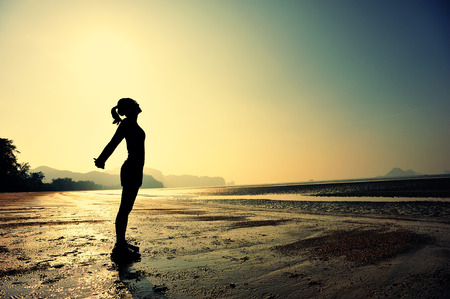 sport silhouette: young woman stretching on sunrise beach