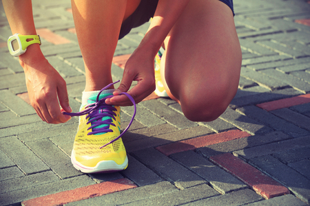 shoelace: young woman runner tying shoelace outdoor Stock Photo