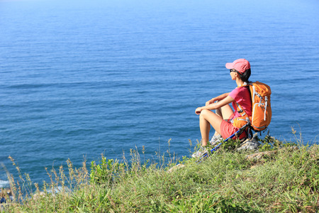 trekker: woman hiker legs hiking on seaside mountain trail