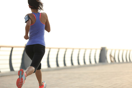 outdoor exercise: young woman runner athlete running at seaside