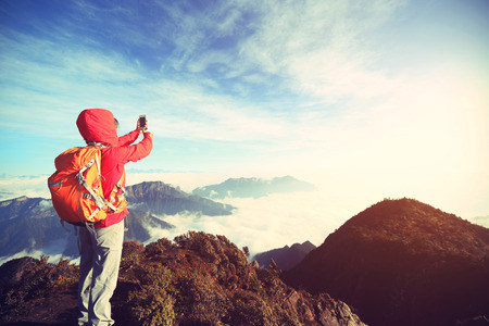 japanese people: young asian woman backpacker taking photo with smartphone on mountain peak Stock Photo