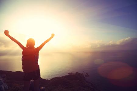 sol radiante: animando mujer joven mochilero al amanecer pico de la montaña junto al mar