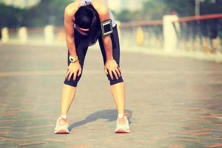 sol radiante: Corredor de la mujer cansada de tomar un descanso después de correr duro en la playa sol