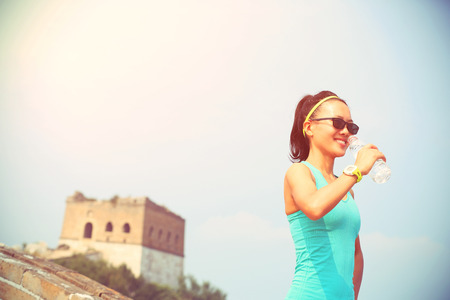country girls: woman runner athlete drinking water after run on chinese great wall.