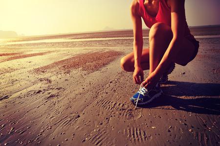 levantandose: corredor de la mujer atar cordones de los zapatos antes de correr en la playa Foto de archivo