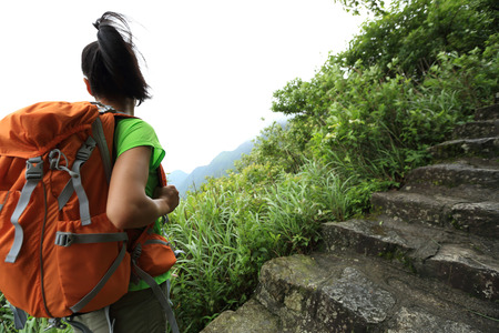 stair climber: young woman backpacker hiking on mountain stairs