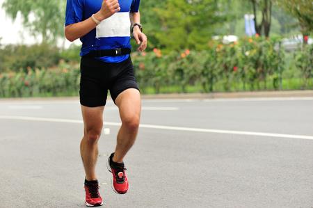 wrist strap: Marathon runner running on city road Stock Photo