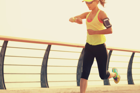 若いフィットネス女性ランナーの海辺でのスマートな腕時計から彼女の実行時間の確認