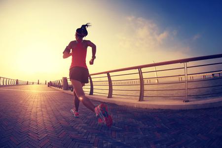 deportista: Runner atleta que corre en la playa. Aptitud de la mujer silueta de la salida del sol para correr entrenamiento concepto de bienestar. Foto de archivo