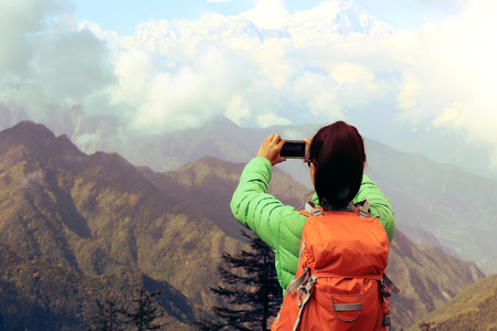 young asian woman backpacker taking photo with smartphone on mountain peak 免版税图像
