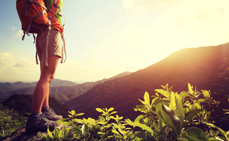 woman backpacker on sunrise mountain peak rock 스톡 콘텐츠
