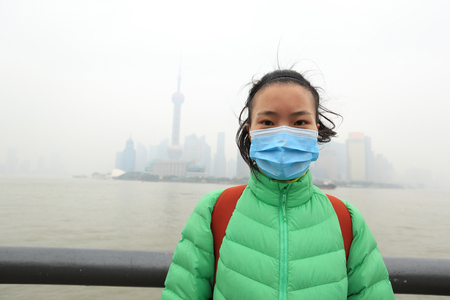 pollution: worried young woman wear a mask at the pollution city Stock Photo