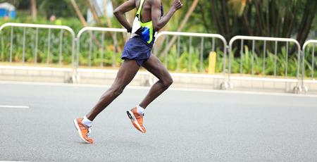 piernas hombre: Marathon runner running on city road Foto de archivo
