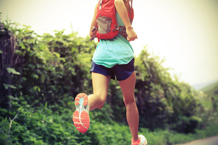 training shoes: trail runner athlete running on forest trail. woman fitness jogging workout wellness concept. Stock Photo