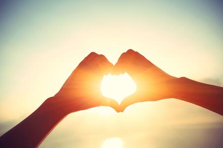 toma la forma del corazón de las manos contra la salida del sol brillante mar y forma de oro de sol en el agua Foto de archivo