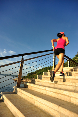 young woman running: young fitness woman runner running on seaside stone stairs