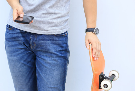 pone: skateboarder use cellphone lean on wall